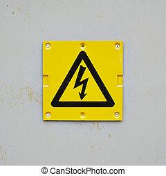 Yellow warning sign on a gray wall