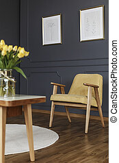 Yellow wooden armchair under posters in grey living room...