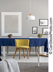 Yellow wooden chair at table with blue cloth in modern dining room interior with mockup. Real photo