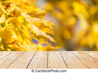 Yellow wooden desk top with golden leaves