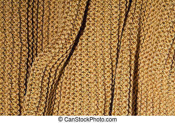 Yellow wool knitted scarf closeup.