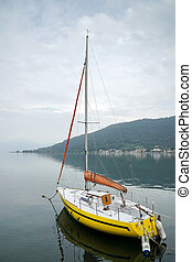 Yellow yacht moored on Lake Iseo at Sarnico