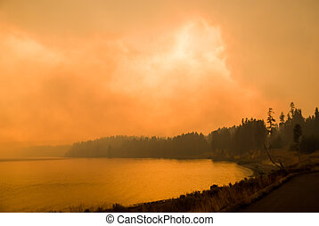 Dense smoke obscures the sky above Yellowstone Lake as a forest fire races toward the shoreline.