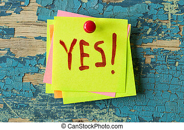 YES text written on sticky note on rustic  background