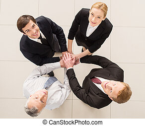 Yes, we are the best! Top view of four cheerful people in formalwear clasping their hands together and looking at camera