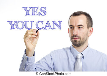 Yes you can - Young businessman writing blue text on transparent surface