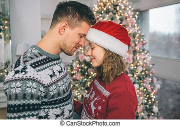 yeux ont fermé, garder, room., couple, paisible, arbre, touchers, forehead., séduisant, ils, chaque, devant, décoré, autre, noël, stand