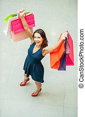 yo, amor, shopping!, punta la vista, de, hermoso, mujer joven, tenencia, bolsas de compras, y, sonriente, en cámara del juez