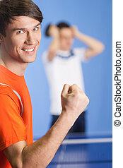 yo, won!, feliz, joven, tenis de mesa, jugador, el gesticular, mientras, el suyo, adversario, posición, en, el, plano de fondo, con, cabeza en manos