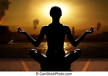 silhouette of woman in a sunset relaxing her mind with yoga near sea port with industry