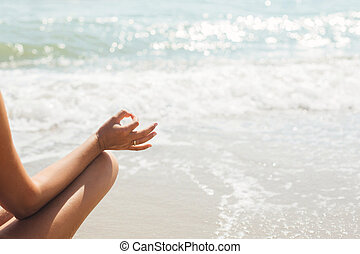 Yoga and meditation on beach at sea. Closeup of woman hand in lotus position on background of sunny waves while practicing yoga and meditating. Mental health and self care