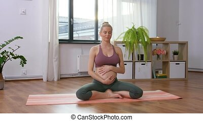 yoga and people concept - happy pregnant woman meditating at home