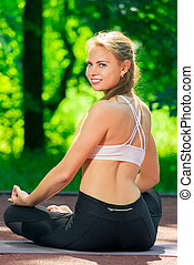 yoga asanas - view of the back of a woman in the lotus position in the park