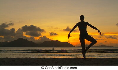 silhouette of woman practising yoga at sunset on tropical island part II