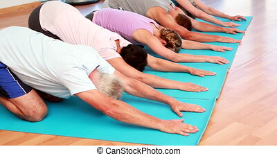 Yoga class in childs pose together at the gym