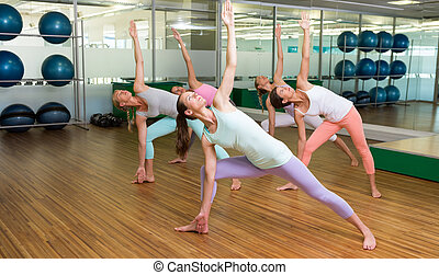Yoga class in extended triangle pose in fitness studio
