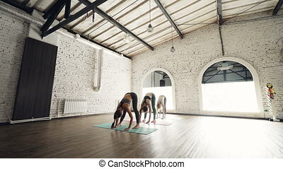 Yoga class is practicing garland pose Malasana and forward...