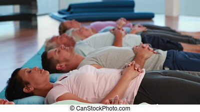 Yoga class lying down in relaxation with eyes closed at the...