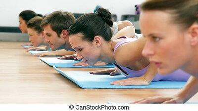 Yoga class lying on mats doing cobra