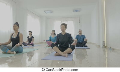 Yoga class made of middle aged women and man meditating in lotus position in a fitness studio