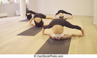 Yoga class. Reclining angle pose - Yoga class. People doing...