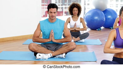 Yoga class sitting in lotus pose to