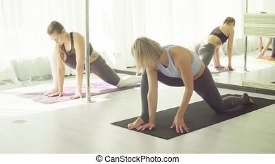 Three women doing yoga exercises in studio.