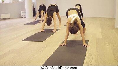 Yoga class. Upward bow pose - Yoga class. People doing yoga...