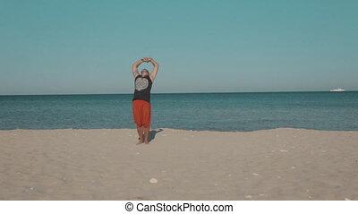 Yoga classes on the deserted ocean shore - Adult male doing...