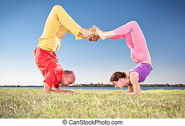 Yoga couple, man and woman doing Vrschikasana scorpion pose...