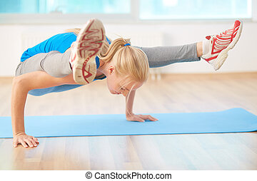 Yoga exercise - Agile blond girl doing yoga exercise in gym