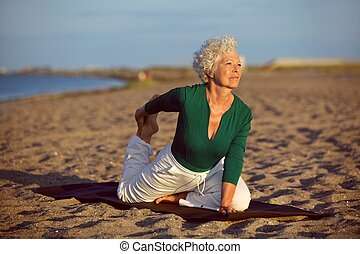 Yoga exercise on the beach - Senior woman in stretching...