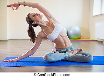 Yoga exercises - Young pretty female exercising in fitness...