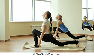 Young women doing yoga exercises one after another at a quick pace