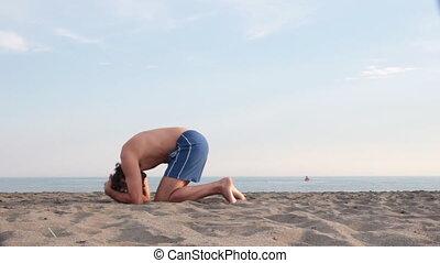 yoga fall - man doing Yoga on the beach ,failing sirsasana