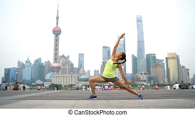 Yoga fitness instructor in urban city outdoors in Shanghai, China. Sport woman in exalted warrior pose 4 etc doing workout class on the Bund boardwalk. Female yogi.