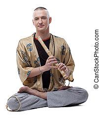 Yoga guru playing flute, isolated on white