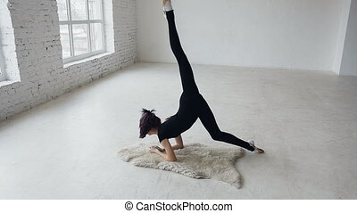 Yoga - gymnastic girl make exercise training in sport school in white background near big windows. Flexibility exercise training. Young fit teenage girl warming up stretching in a gym. The girl dressed black bodysuit