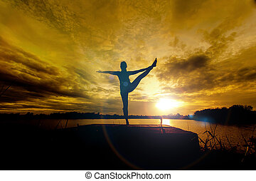 Yoga in silhouette with dramatic sunset sky background
