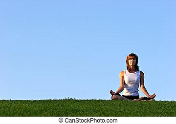 Attarctive woman practicing yoga outdoors