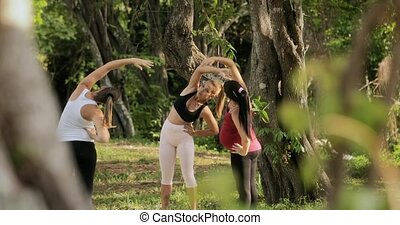Yoga Instructor Exercising With Pregnant Women In Park