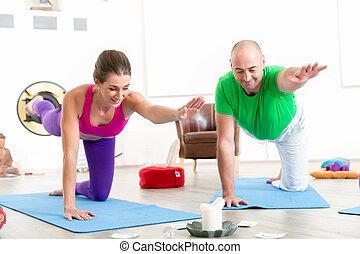 Yoga instructor teaching bird dog pose to woman - Smiling ...