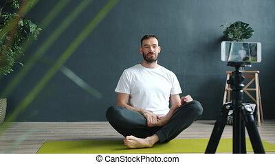 Yoga instructor teaching online recording tutorial in studio...
