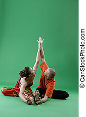 Yoga. Man and woman performing paired asana
