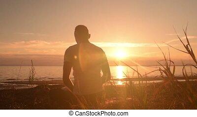 Yoga man sitting on the beach and meditating