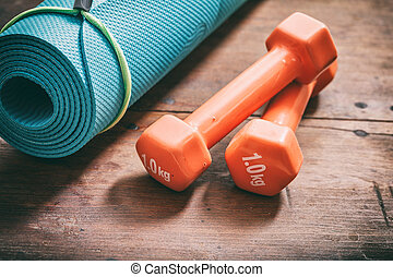 Yoga mat and dumbbells on wooden background - Green yoga mat...