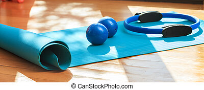 Yoga mat and exercise weights on wooden floor