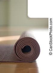 Yoga Mat - Simple close up of a yoga mat rolled up in a yoga...