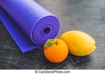 Yoga mat, water, orange and mango on a wooden background. Equipment for yoga. Concept healthy lifestyle, diet and sport. Copy space. Selective focus