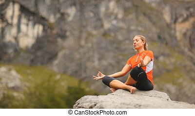 yoga on rock - woman practicing yoga on rock in the...